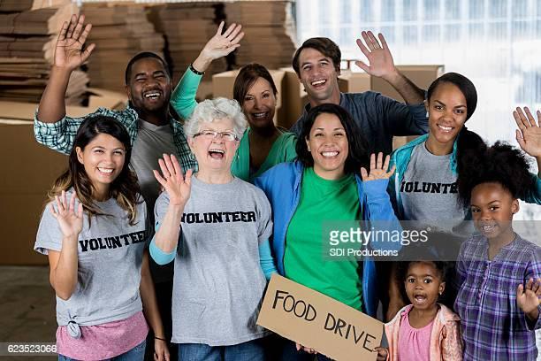 Group of cheerful volunteers waving during food drive