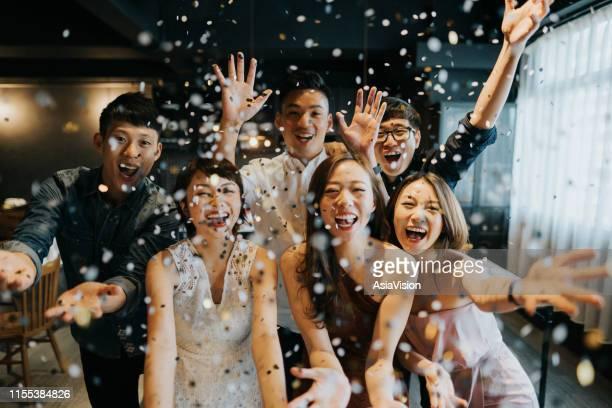 パーティー中に紙吹雪で祝う陽気な若いアジアの男女のグループ - 小道具 ストックフォトと画像