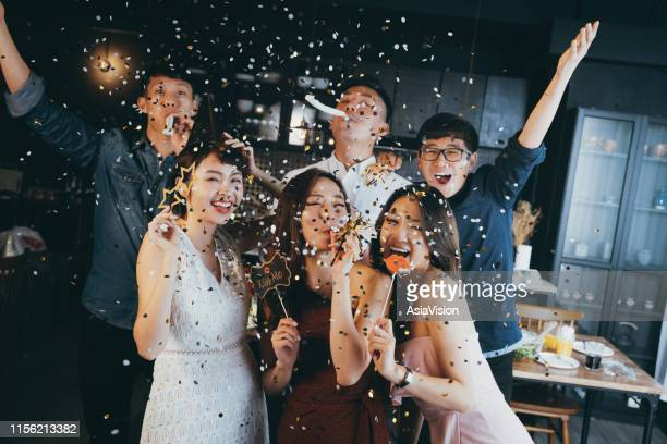 group of cheerful young asian man and woman holding props and celebrating with confetti during party - asia stock pictures, royalty-free photos & images