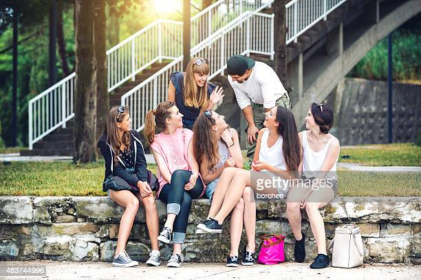 Group Of Cheerful Young Friends Gathering In Park