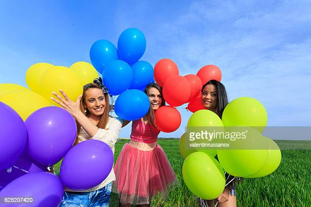 Group of cheerful young women holding multicolored balloons