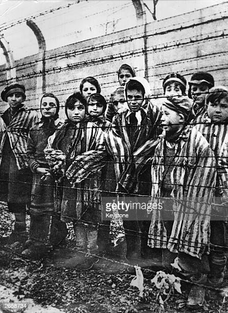 Group of child survivors behind a barbed wire fence at the Nazi concentration camp at Auschwitz-Birkenau in southern Poland, on the day of the camp's...