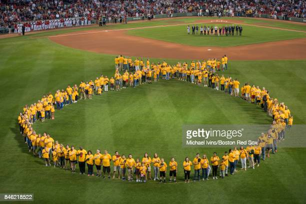 A group of childhood cancer survivors and their families form a human ribbon in center field during a ceremony in recognition of childhood cancer...