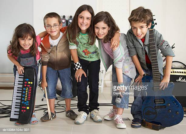 group of children (7-10) acting as rock band standing with instruments, portrait - garage band stock photos and pictures