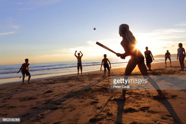 Group of children and adults playing ball game on beach at sunset