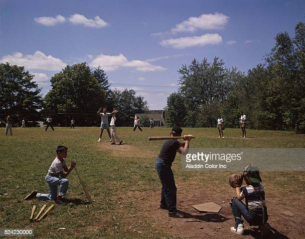 A group of children and adults playing baseball on the grounds of the Kenmore Hotel