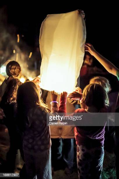 CONTENT] A group of children and adults releasing Chinese lanterns at night