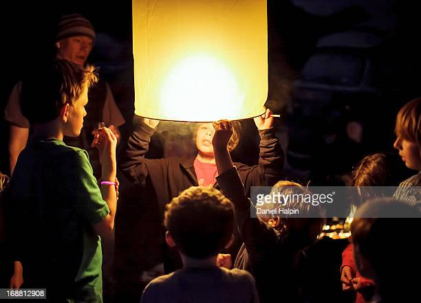 Group of children and adults releasing Chinese lanterns at night.