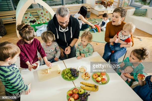 group of children and teachers preparing fruit in kindergarten - kindergarten stock-fotos und bilder