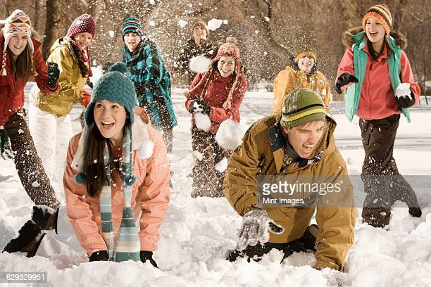 a group of children and young people having a snowball fight. - medium group of people stock pictures, royalty-free photos & images
