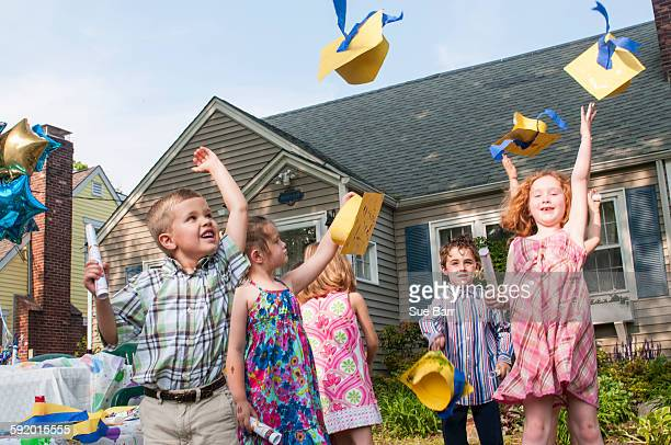 Group of children at kindergarten graduation, throwing paper mortar boards in air