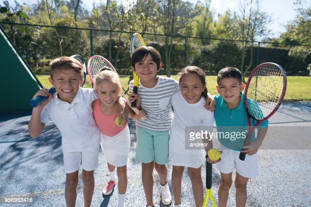 Group of children at the tennis court embracing each other and holding their rackets looking at camera smiling