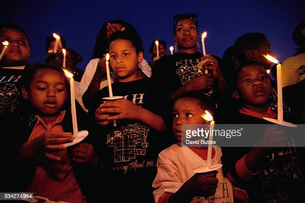 Group of children attend a candlelight vigil one year after the Los Angeles riots. In April of 1992, after a jury acquitted the police officers...