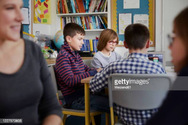 group of children behind a teacher in a classroom during a lesson - primary age child stock pictures, royalty-free photos & images