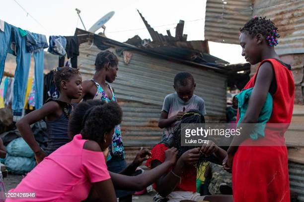 A group of children braid a girl's hair inside the Povoado slum on January 27 2020 in Luanda Angola In June 2013 3000 families were evicted from a...