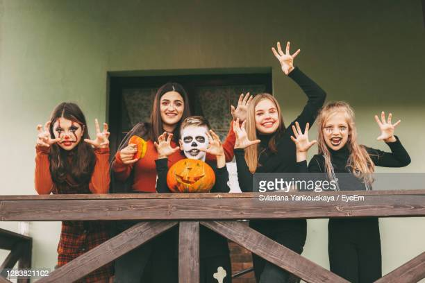 a group of children celebrating halloween on the street near the house in nature in costumes - 12 17 months stock pictures, royalty-free photos & images