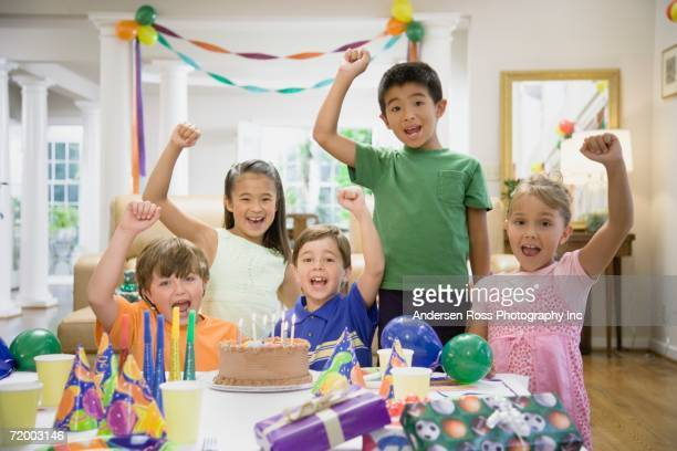group of children cheering at birthday party - happy birthday images for sister stock pictures, royalty-free photos & images