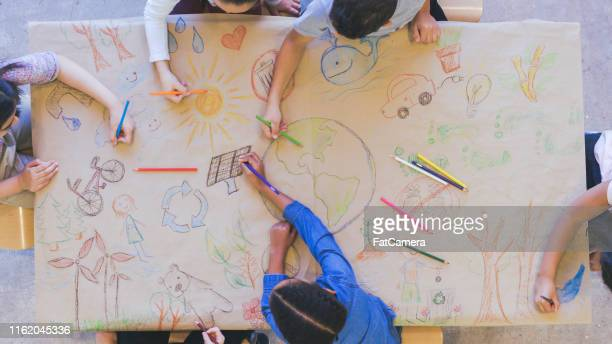 group of children color environmentally conscious mural - global village stock pictures, royalty-free photos & images
