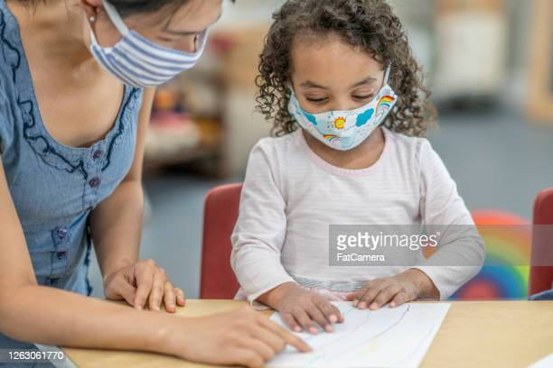 group of children colouring while wearing masks - montessori education stock pictures, royalty-free photos & images