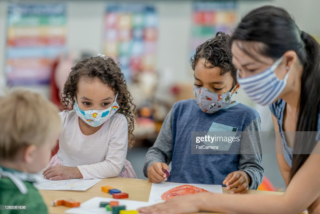 Group of children colouring while wearing masks : Stock Photo