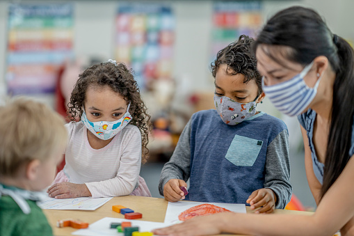 Group of children colouring while wearing masks 1263061836