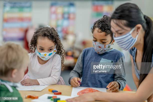 group of children colouring while wearing masks - preschool child stock pictures, royalty-free photos & images