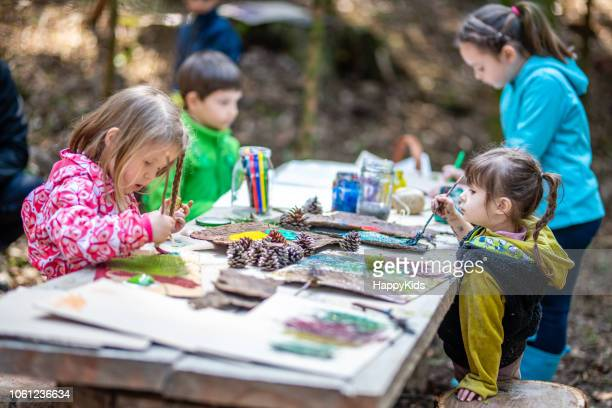group of children doing painting - multi colored coat stock photos and pictures
