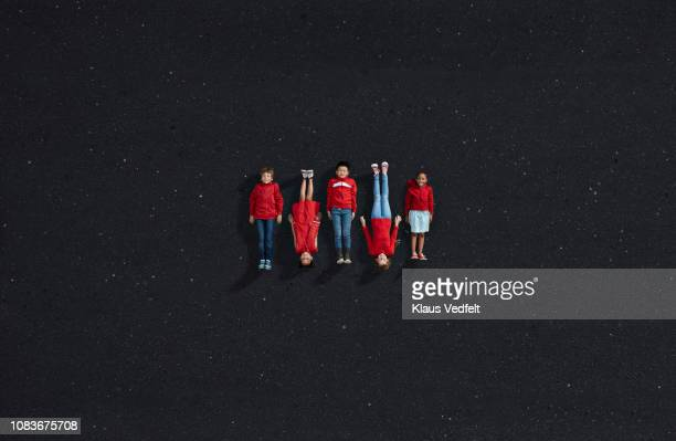 Group of children dressed in red, laying on dark asphalt surface