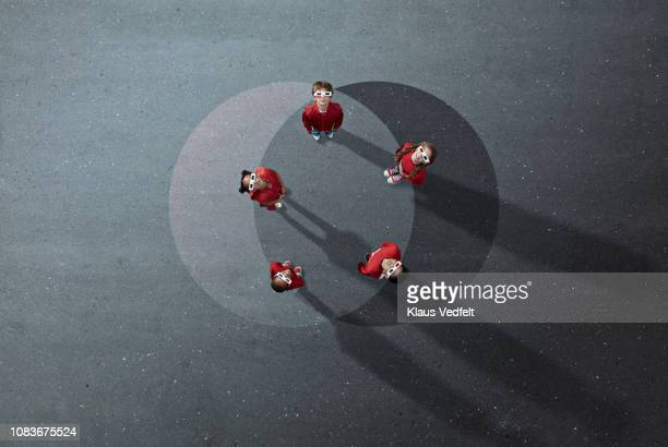 Group of children dressed in red standing on painted circles, wearing 3-D glasses