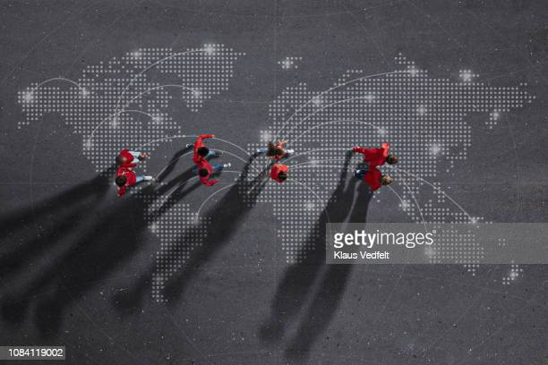 Group of children dressed in red, walking across world map