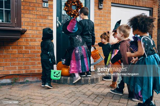 a group of children dressed up for halloween at a front door with buckets trick or treating. - halloween stock pictures, royalty-free photos & images