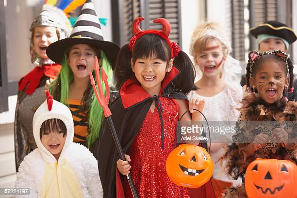 group of children dressed up in costumes for halloween - halloween kids stock photos and pictures