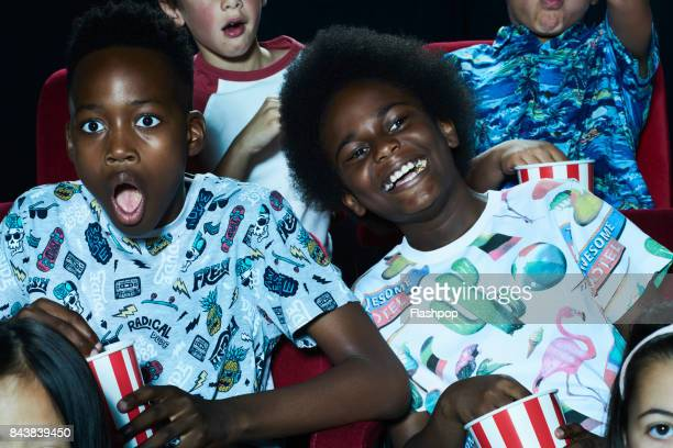 group of children enjoying a movie at the cinema - graphic t shirt stock pictures, royalty-free photos & images