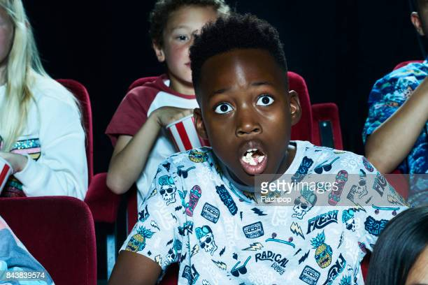group of children enjoying a movie at the cinema - children theatre stock photos and pictures