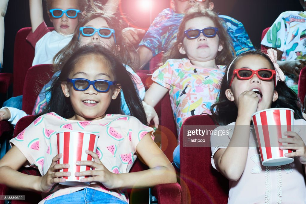 Group of children enjoying a movie at the cinema : Stock Photo