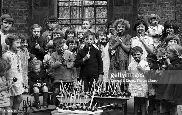 Group of children enjoying toffee apples outside a terraced house One is sitting in a pushchair