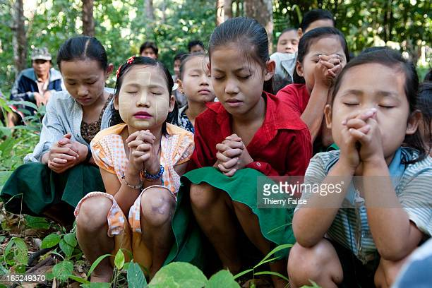 A group of children from a nearby village prays while waiting for a Free Burma Rangers relief group to provide medical treatment The FBR is a group...