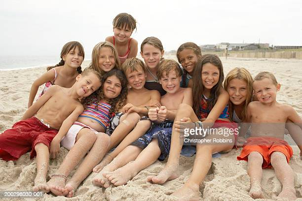 Group of children (3-12) gathered on beach, portrait