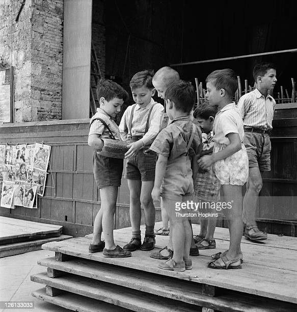 A group of children gathered round one of their number who has his forearm inside a marrow San Gimignano Tuscany Italy August 1955 Original...