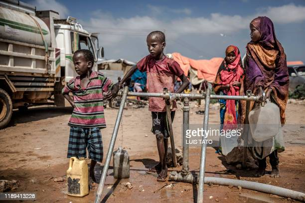 TOPSHOT A group of children get water from water taps at the water distribution point of a displacement camp for people affected by intense flooding...