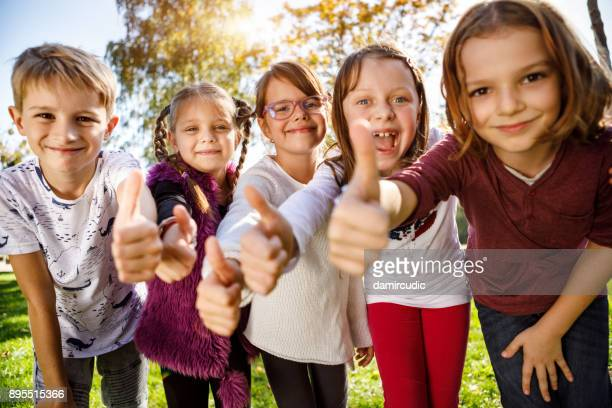 group of children giving thumbs up - charity and relief work stock pictures, royalty-free photos & images