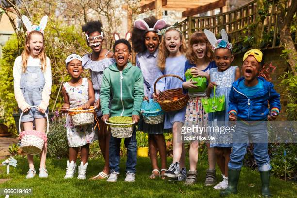 group of children having fun on an easter egg hunt. - chasse aux oeufs de paques photos et images de collection