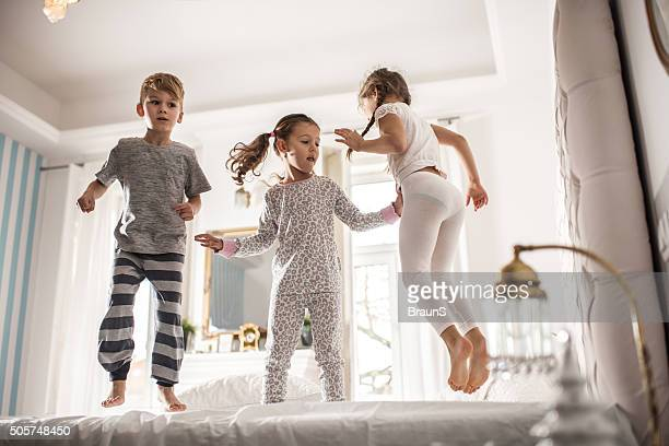 group of children having fun while jumping on a bed. - pyjama stockfoto's en -beelden