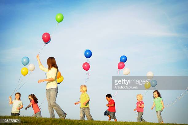Group of Children Holding and Running with Balloons