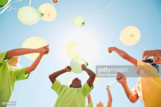 group of children holding balloons outdoors - releasing stock pictures, royalty-free photos & images