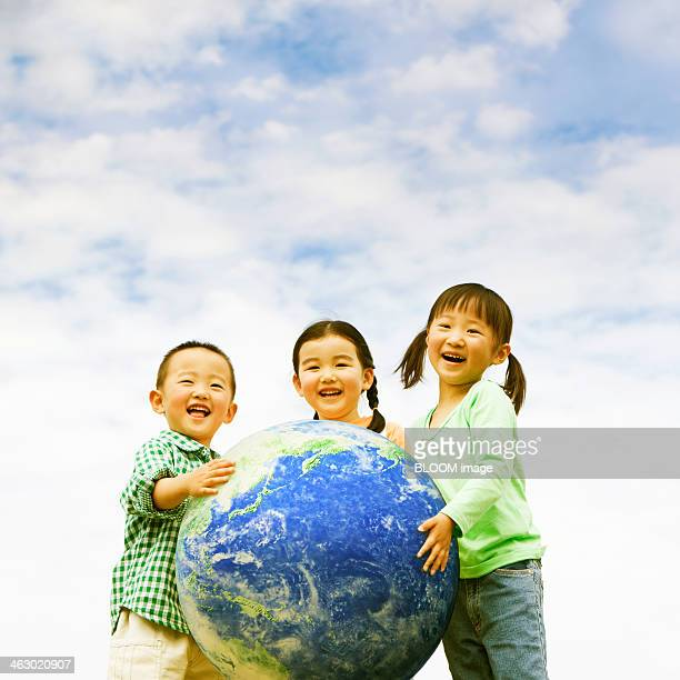 Group Of Children Holding Earth