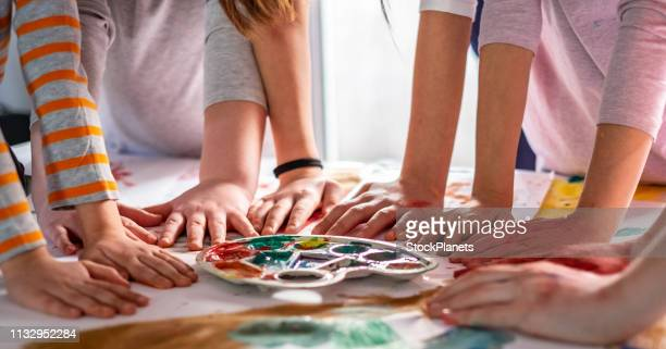 grupo de niños sosteniendo las manos en la mesa después de dibujar - art and craft fotografías e imágenes de stock