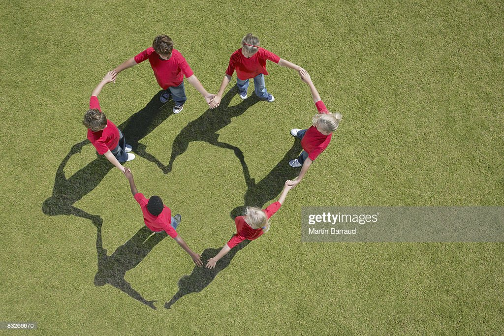 Group of children holding hands in heart-shape formation : Stock Photo