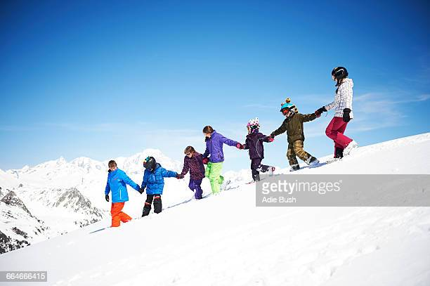Group of children holding hands on snowy slope