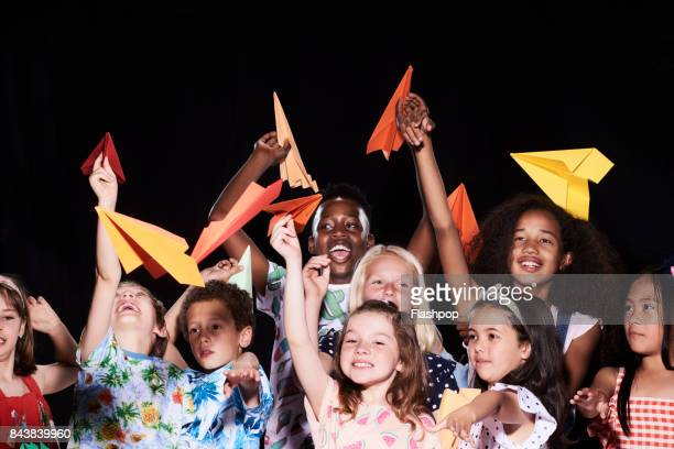 Group of children holding paper airplanes